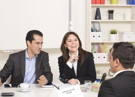 仕事: 就職の面接で経営陣に彼女のプロフィールについて説明する男 写真素材