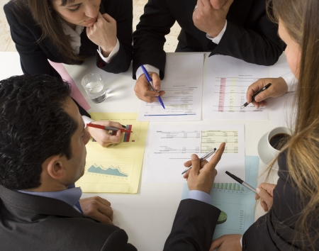 team working together: Businesspeople working together at meeting, discussing document Stock Photo