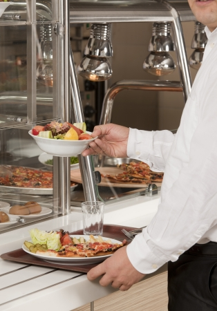 buffet self-service food display human hand take plate photo