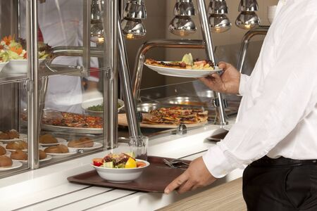 buffet lunch: buffet self-service food display human hand take plate Stock Photo