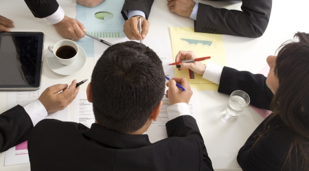 Boardroom meeting: Businesspeople working together at meeting, discussing document Stock Photo