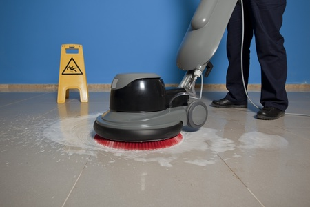 cleaning an office: cleaning floor with machine Stock Photo