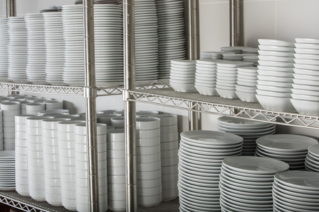 dish: Stacks of many white plates on a wire rack shelf in a commercial kitchen