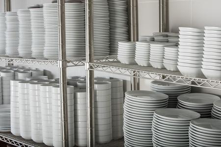 Stapels van de vele witte platen op een rooster plank in een commerciële keuken