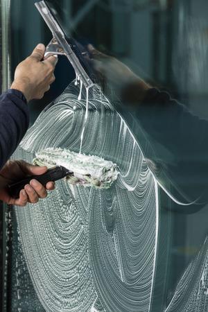 창문을 닦기 위해 스퀴지를 사용하는 창 클리너 스톡 콘텐츠