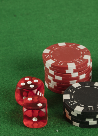 two red dices and different chips on green background. gambling and betting addiction concept Stock Photo