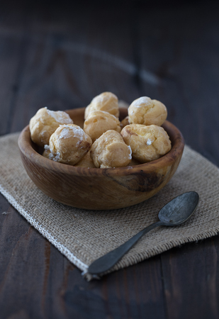 profiterole in wooden plate on dark background Stock Photo