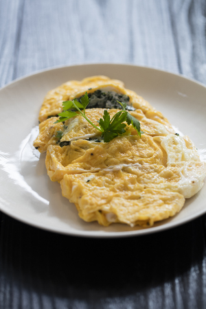 omelet with spinach on white plate on dark background Stockfoto