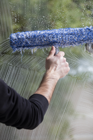 a soapy window with a squeegee cleaning the glass Stock Photo