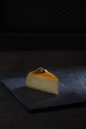 one slice of pumpkin cheesecake over dark background