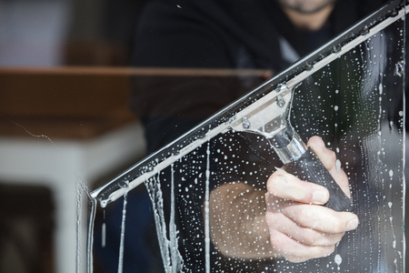 a soapy window with a squeegee cleaning the glass Standard-Bild