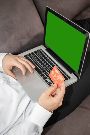 Young man buying goods from the internet and entering number security code from credit card on laptop with green screen. Online, technology and internet concept. Banque d'images - 144136309