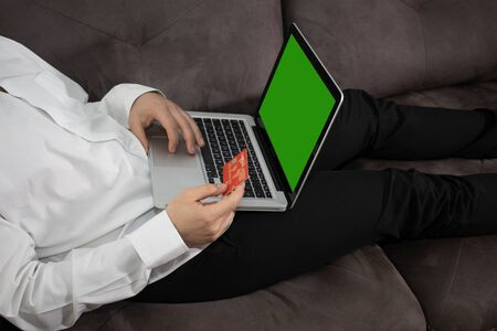 Young man buying goods from the internet and entering number security code from credit card on laptop with green screen. Online, technology and internet concept. Banque d'images - 144136394