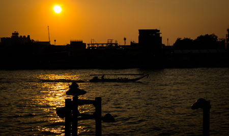 highriser: silhouette  Skyline at sunset at chao phraya river in bangkok thailand.