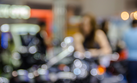 scrambler: abstract blurred beautiful woman in motorcycle showroom.