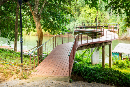Wooden old bridge link to the relax garden park zone in vintage stye within resort and forest river landscape. Stock Photo