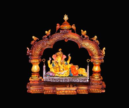 Beautiful hindu god ganesh statue isolated on black background. Banco de Imagens