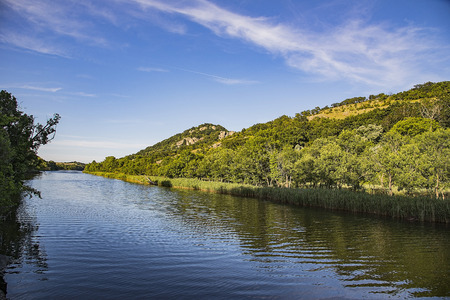 Calm river flowing at the foot of a high rocky hill Stock Photo