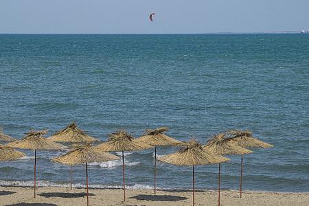 Strand. Reed paraplu's. Kitesurfer zwemt in de open zee