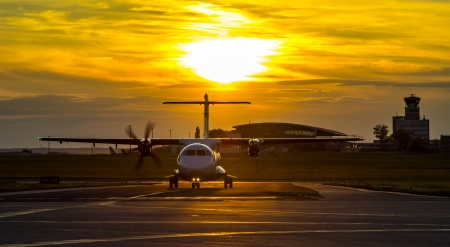 Propeller plane taxiing around the airport at sunset
