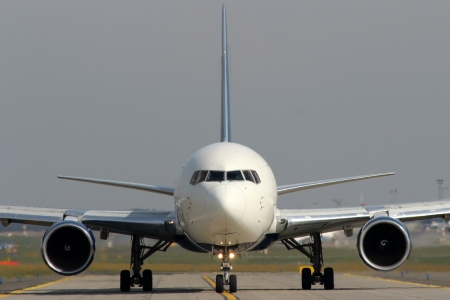 White aircraft on taxiway at airport