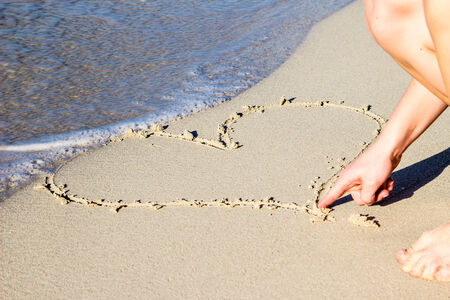 Girl finger painting hearts in the sand photo