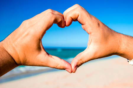 Heart made ​​of hands at the beach with the ocean on background photo