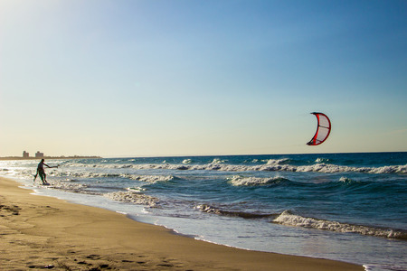 kite surfing: A man goes to his Kite Board on the beach