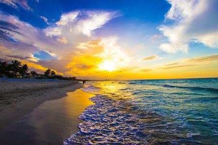 Sandy beach with the ocean at sunset Standard-Bild