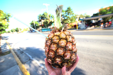 Hand holding a drink in the fresh pineapple towards the street photo