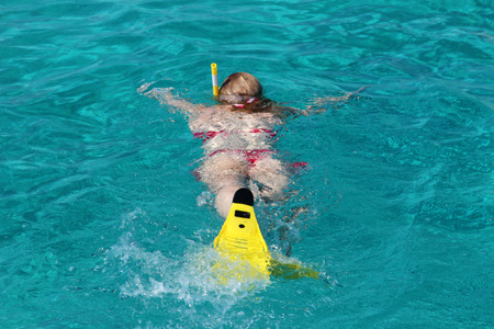Beautiful young girl snorkeling in the ocean photo