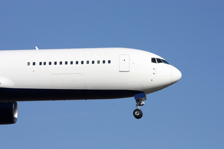 Nose of huge white airplane landing on blue sky photo