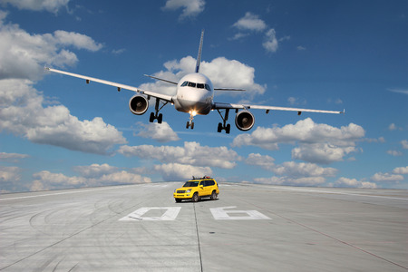 View on the threshold of runway 06 with follow me car and a passing plane photo