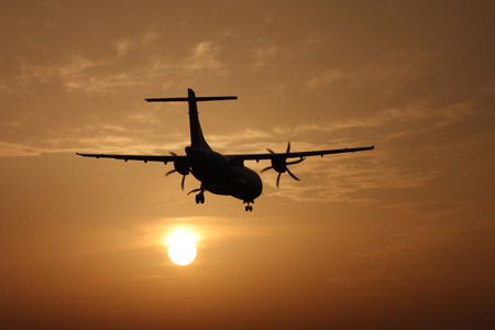 Small transport propeller airplane landing at sunset