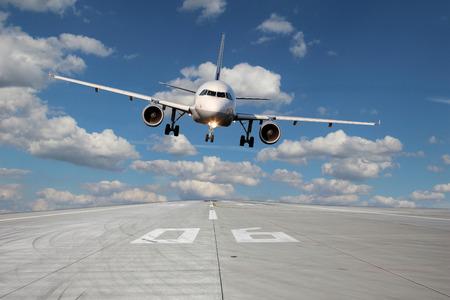 Aircraft passa basso sopra la pista 06 con belle nuvole sullo sfondo Archivio Fotografico - 26349560