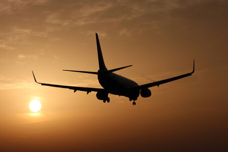 Small transport jet airplane landing at sunset photo