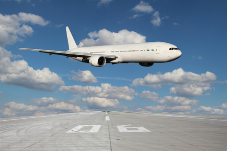 fuselage: White plane makes a low pass over the airport runway Stock Photo