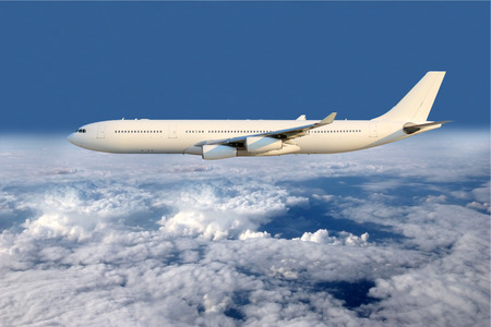 Large white plane flying above the clouds Stock Photo