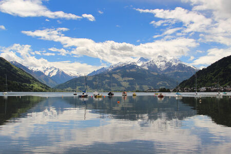 Anchored boats on the lake of Zell am See with beautiful summer alpine mountains in the background photo