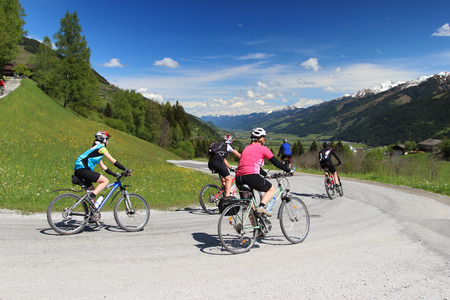 Group of cyclists descended the hill in Austrian Alps