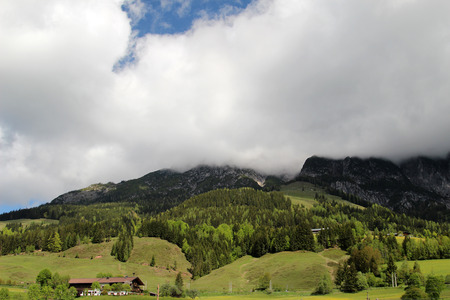 Summer Austrian Alps with mountains disappearing in the clouds photo