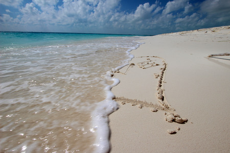miss you: The wave washes away the sand in the heart with the word LOVE Stock Photo