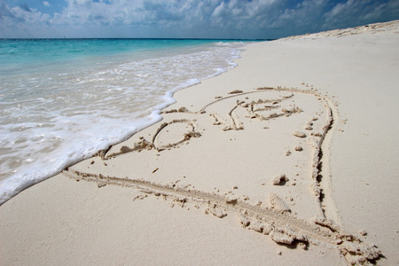 Heart in the sand on the beach with the word LOVE photo
