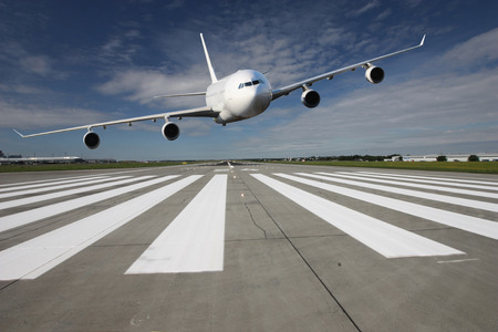 White airplane overflights low over the runway threshold Stock Photo