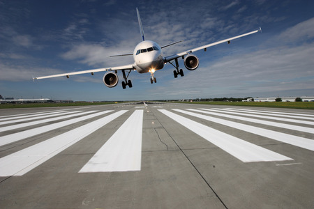 aircraft aeroplane: Landing aircraft low over the runway with stretched landing gear