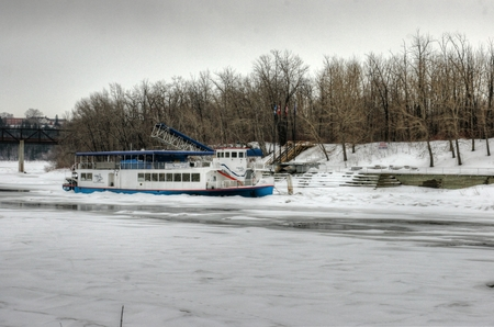 frozen river: Edmonton boat stuck in frozen river in winter Editorial