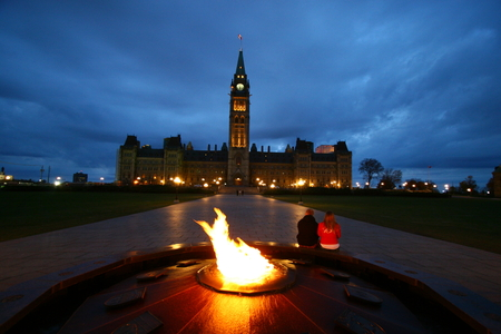 centennial: A couple sitty beside the Centennial Flame  looking at Ottawa Parliament Stock Photo