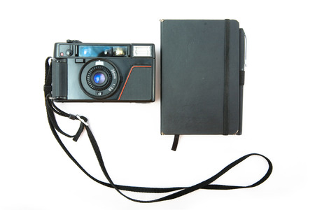 Film camera and note pad on white photo