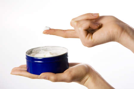 cosmetic cream and hand on white photo