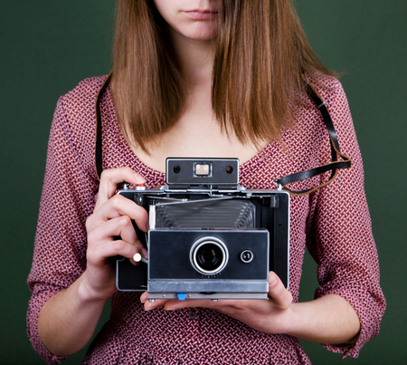 vintage camera in the hands of the girl photo